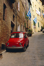 Red car parked in narrow street, Siena, Tuscany, Italy
