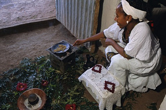 Woman roasting beans for coffee ceremony, Lalibela, Wollo region, Ethiopia, Africa