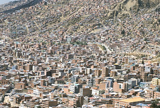 View across city from El Alto, of suburb houses stacked up hillside, La Paz, Bolivia