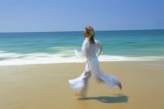 Woman running along beach, Kovalam, Kerala state, India, Asia