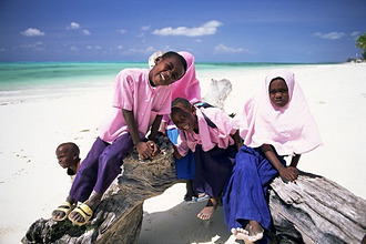 Young Muslim children in school uniform on beach at Jambiani, Zanzibar, Tanzania, Africa