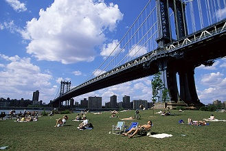 People sunbathing at a park in Brooklyn under the Manhattan Bridge, New York, New York State, United States of America, North America