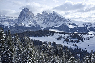 A snowy view of Sassolungo and Sassopiato Mountains behind the Alpe di Siusi ski area in the Dolomites, South Tyrol, Italy, Europe