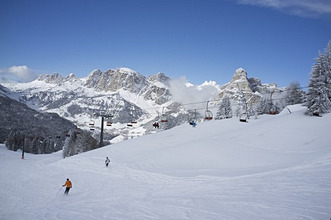 Skiers at the Alta Badia ski resort with Sassongher Mountain in the distance, Dolomites, South Tyrol, Italy, Europe