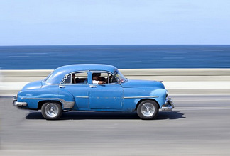 Panned' shot of old blue American car to capture sense of movement, with the Caribbean Sea in the background, The Malecon, Havana Centro, Cuba, West Indies, Central America