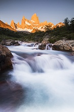 Sunrise Mount Fitz Roy (Cerro Chalten) and waterfall seen on Lago de los Tres hike, UNESCO World Heritage Site, El Chalten, Patagonia, Argentina, South America