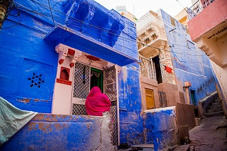 Woman standing in front of her blue house in Jodhpur, the Blue City, Rajasthan, India, Asia