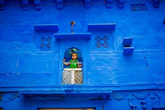 Little girl standing in her window in the blue houses of Jodhpur, the Blue City, Rajasthan, India, Asia