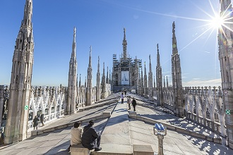 Tourists among the white marble spiers on the top of the Duomo, Milan, Lombardy, Italy, Europe