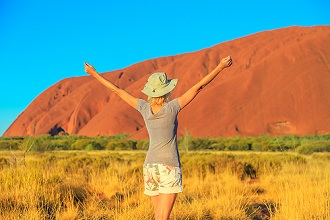 Carefree tourist woman with raised arms enjoys Uluru (Ayers Rock) at sunset in Uluru-Kata Tjuta National Park, UNESCO World Heritage Site, Northern Territory, Australia, Pacific