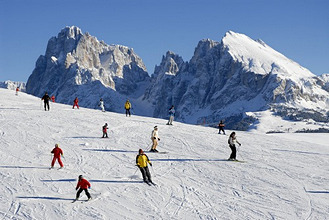 Skiers on a ski slope under blue sky, Alpe di Siusi, Valle Isarco, South Tyrol, Italy, Europe