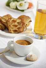 A cup of espresso, apple juice and pastries