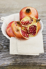 Pomegranate, whole and halved, on cloth in white bowl