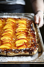 Hands holding a peach tart on a baking tray