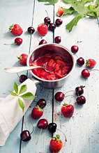 Strawberry jam in a pot, fresh cherries and strawberries