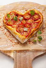 A heart-shaped pizza topped with tomatoes