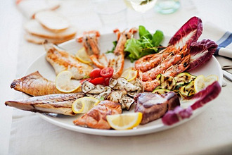 A plate of grilled food including seafood, fish and vegetables