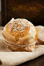 Sesame seed roll wrapped in baking parchment