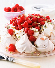 Pavlova Topped with Whipped Cream, Raspberries and Powdered Sugar