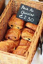 Chocolate croissants in a basket with a price tag