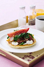 A pancake topped with ricotta, spinach and bacon, for breakfast