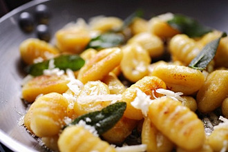 Gnocchi with sage and parmesan in a frying pan (close-up)