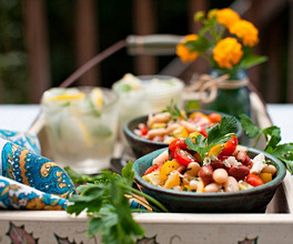 Bowls of Bean and Tomato Salad with Feta Cheese on a Tray with Drinks on an Outdoor Table