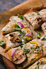 Veggie Pizza with Mushrooms, Red Onion and Yellow Peppers; Fresh Basil; Sliced on Parchment Paper