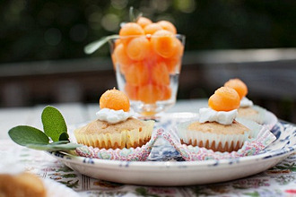 Muffins Topped with Melon Balls; On an Outdoor Table