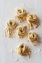 Nests of flat noodles on a floured worktop (view from above)