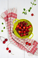 Fresh cherries in a green colander