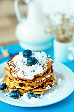 Gluten-free corn pancakes with blueberries and icing sugar