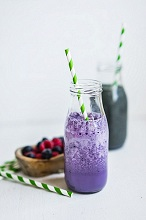 A blueberry smoothie in a bottle with a straw