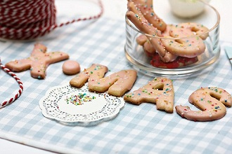 Letter-shaped biscuits decorated with sugar sprinkles spelling XMAS