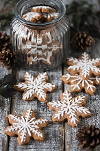 Gingerbread snowflake biscuits decorated with icing, some in a jar