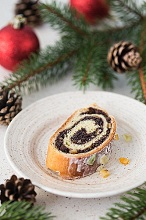A slice of a traditional Polish poppy seed roll cake with icing, dried fruits and nuts