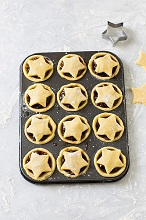 Unbaked Christmas mince pies in a muffin tin