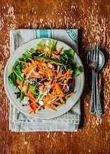 Spinach salad with grated carrots, courgette and raisins