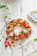Profiterole wreath with whipped cream and strawberries with fresh mint
