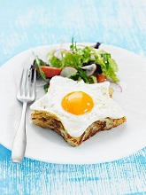 Star-shaped Spanish omelette topped with a fried egg, with a side salad