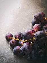 Fresh dark grapes on metal tray background