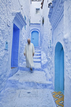 Man in traditional Moroccan clothes walking down painted blue and steps, Chefchaouen, Morocco, North Africa, Africa