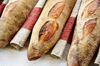 Three baguettes in a row on a linen cloth