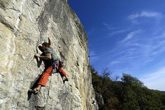 Man climbing up a rock way called Veleno, difficulty 7b, length 15m, Falesia dei forestieri, Montebracco, Sanfront, Cuneo, Piedmont, Italy, Europe