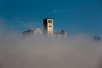 Vew of the steeple of the Basilica of St. Francis with the typical autumn fog, Assisi, Umbria, Italy, Europe