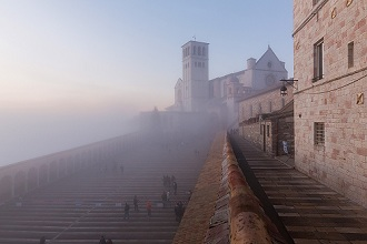 View of the Basilica of St. Francis in the fog at sunset, Assisi, Umbria, Italy, Europe