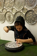 Persian girl chiselling a silver plate, Isfahan; Iran, Middle East