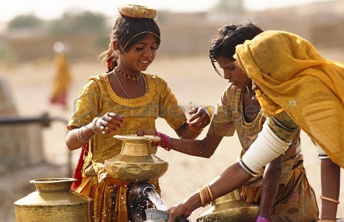 Tribal women and girls collecting water from a well in the desert near Jaisalmer, State of Rajasthan, India