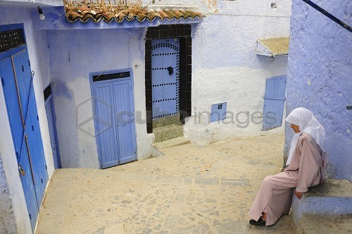 Woman resting in the bluish Chefchaouen medina. Morocco