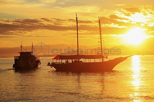 Brazil, Rio de Janeiro State, Angra dos Reis, Ilha Grande, a fishing boat and a schooner silhouetted against the sunset over the Costa Verde (Green Coast)